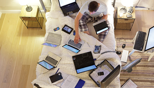 Man sitting on bed surrounded by laptops while working